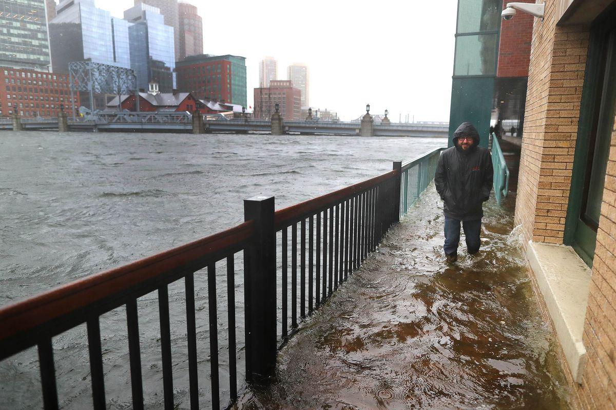 A flooded sidewalk next to a city shoreline, and there's a man in a windbreaker on the sidewalk.