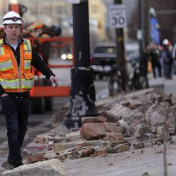 A worker walks by debris from a building on the corner of 400 West and 500 South in Salt Lake City after a 5.7 magnitude earthquake centered in Magna hit early on Wednesday, March 18, 2020.