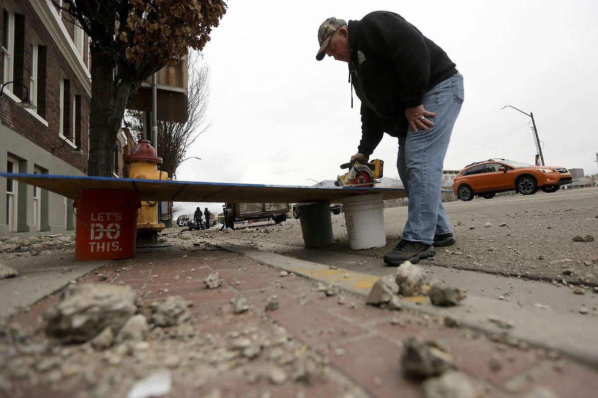 Dave Smith saws wood to board up windows that broke at Caffe Molise and BTG Wine Bar in Salt Lake City after a 5.7 magnitude earthquake centered in Magna hit early on Wednesday, March 18, 2020.
