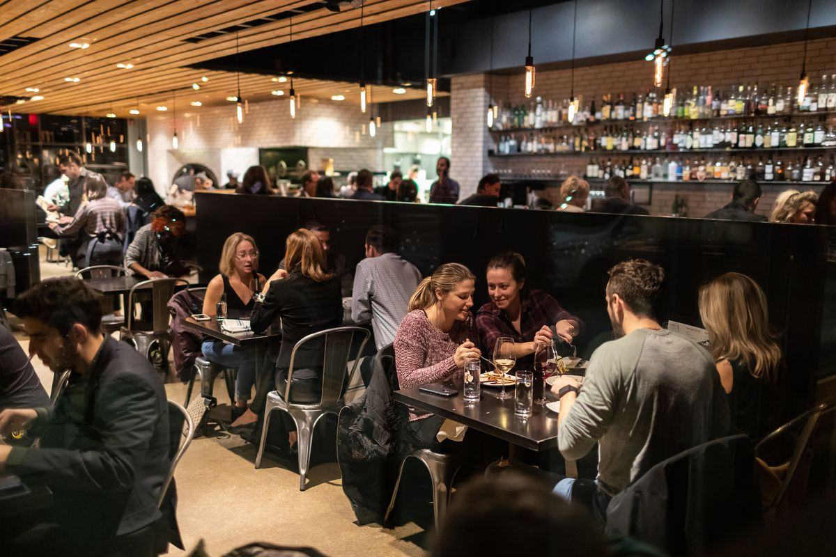 A busy restaurant with a low-black wall separating diners from the bar area.