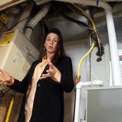 Certified green specialist Catrina Nelson shows a tankless water heater at Garbett Homes in South Jordan on Tuesday, March 12, 2013.