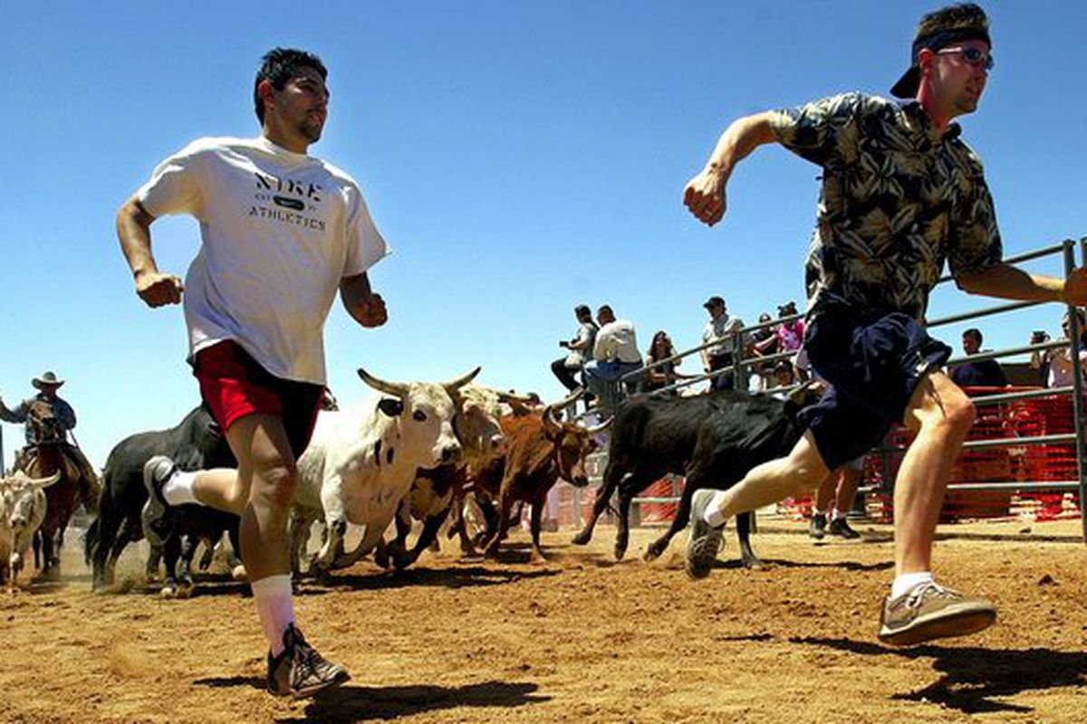Two runners participate in the 2002 edition of Running of the Bulls. The event returns next weekend from a near decade-long hiatus.