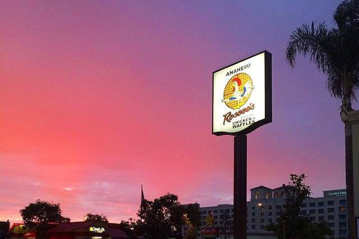 A pink sunset halos around a Roscoe's Chicken & Waffles sign, lit up.