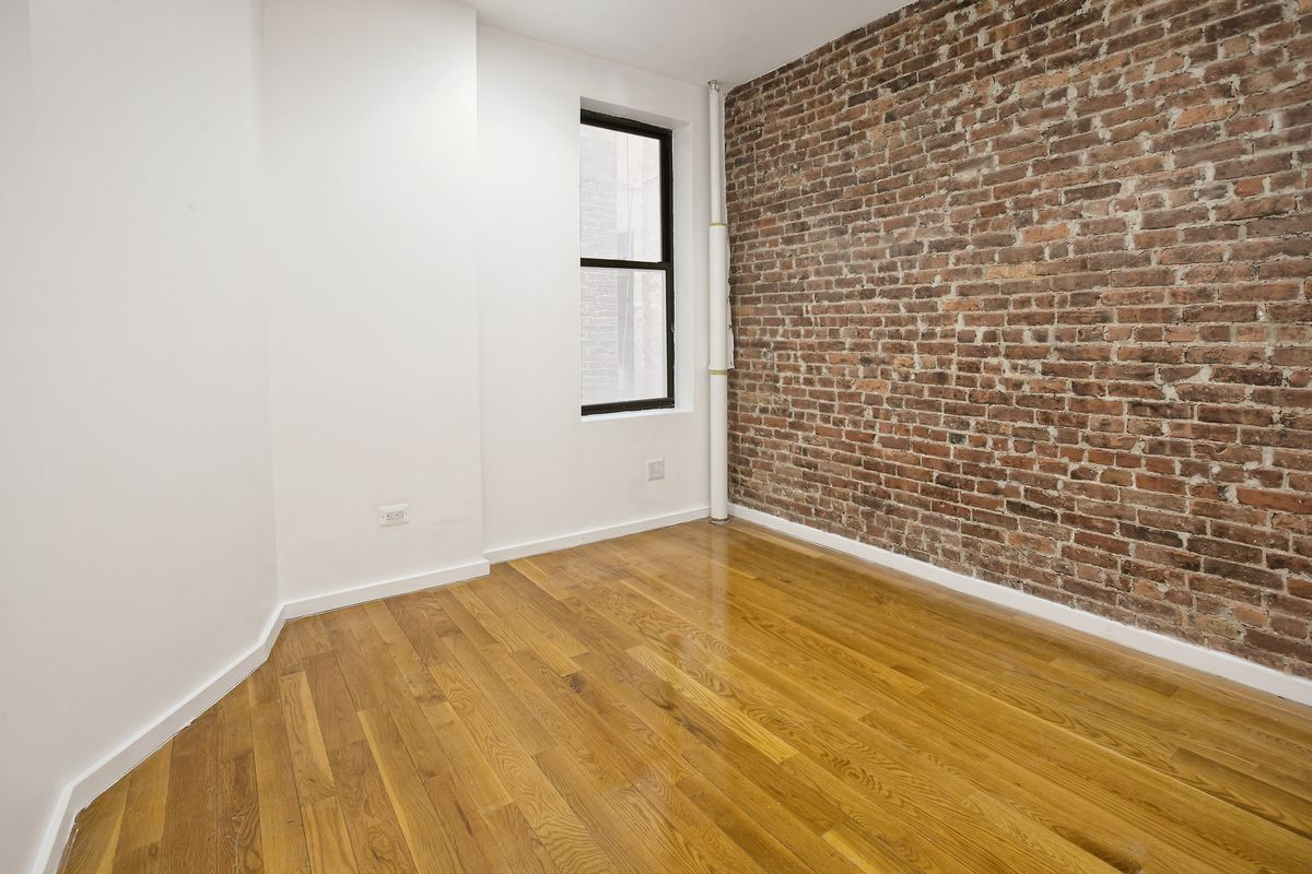 A bedroom with exposed brick, hardwood floors, white walls, and one window.