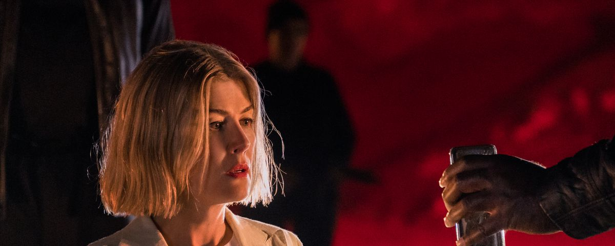 Rosamund Pike looks uncomfortable as a gloved offscreen hand offers her a dark can of something in I Care a Lot