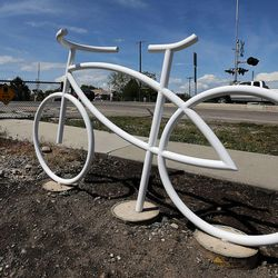 A cyclist passes by a ghost bike memorial in honor of Douglas Crow in Provo, Wednesday, May 20, 2015. Crow was an avid cyclist who died Feb. 13, 2013.