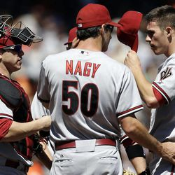 Arizona Diamondbacks starting pitcher Patrick Corbin, right, gets a visit to the mound from pitching coach Charles Nagy and catcher Miguel Montero after Corbin gave up a two-RBI triple to San Francisco Giants' Hunter Pence during the first inning of a baseball game, Monday, Sept. 3, 2012, in San Francisco.