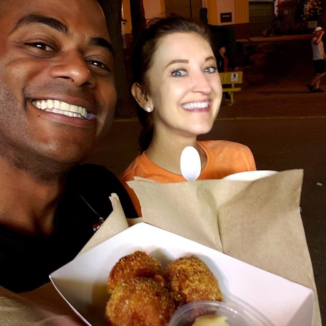 A grinning Jared Brewingtons holds up three crispy fried balls with a creamy sauce in a paper boat