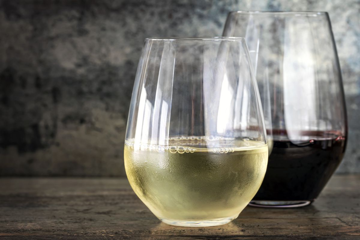 A stemless wine glass filled with white wine in front of a stemless glass filled with red wine