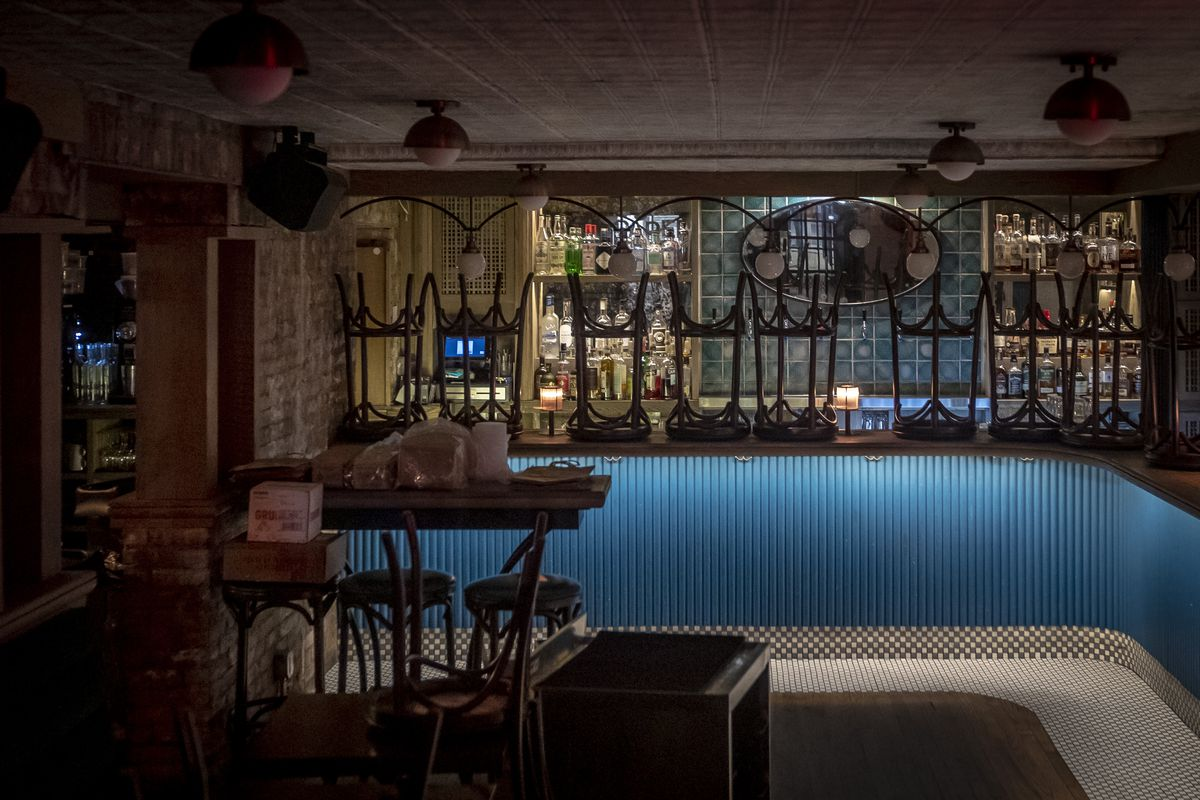 A dark restaurant space with chairs upturned on the bar and not a single person in the room