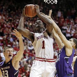Indiana's Noah Vonleh (1) puts up a shot against Northwestern's Kale Abrahamson (13) and Sanjay Lumpkin (34) during the second half of an NCAA college basketball game Saturday, Jan. 18, 2014, in Bloomington, Ind. Northwestern defeated Indiana 54-47. (AP Photo/Darron Cummings)