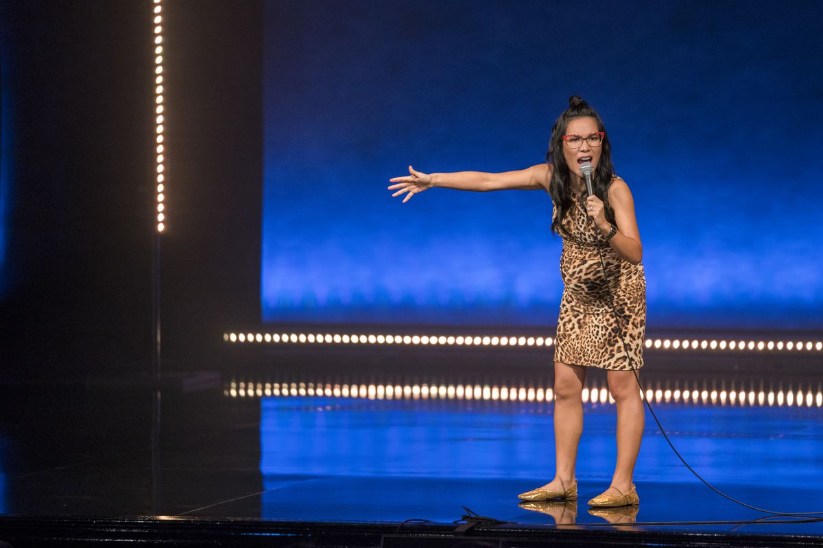 Ali Wong holds out her arm while yelling into a microphone in her Netflix stand-up special, Hard Knock Wife