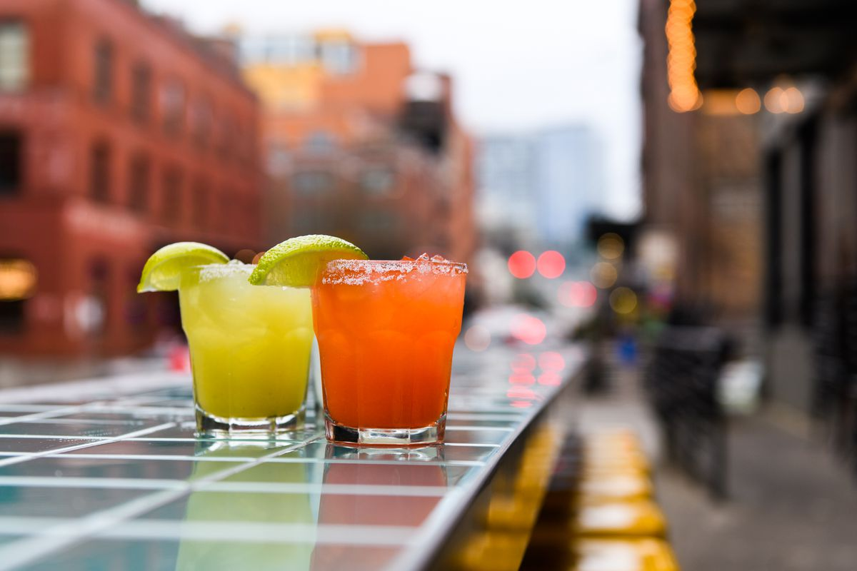 Two margaritas sit on the outdoor bar of Papi Chulo's, lined with turquoise tile. The margaritas are batched and come in strawberry-lime, traditional lime, and pepper