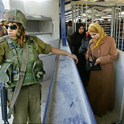 An Israeli army soldier stands guard at a checkpoint as Palestinian women wait in line to cross into Israel at the West Bank city of Nablus.