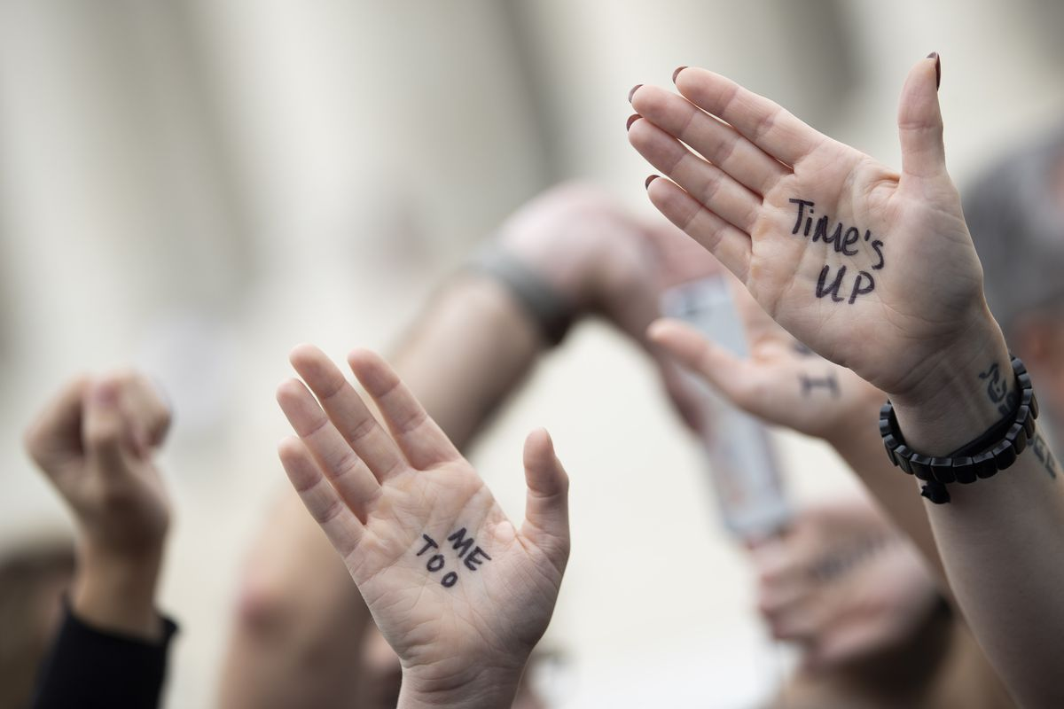 """People raise their hands with the messages """"Time's up"""" and """"Me too"""" inked on them."""