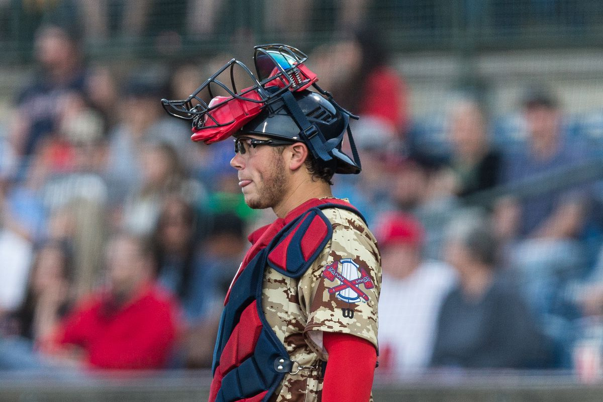 Logan Brown, catcher for the Rome Braves, stands with his mask lifted up onto his forehead. He is wearing sports goggles and sticking his tongue out. The Braves are wearing their camouflage uniforms.