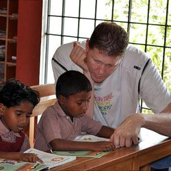 Shawn Bradley helps children with their studies at the Rising Star Outreach campus.