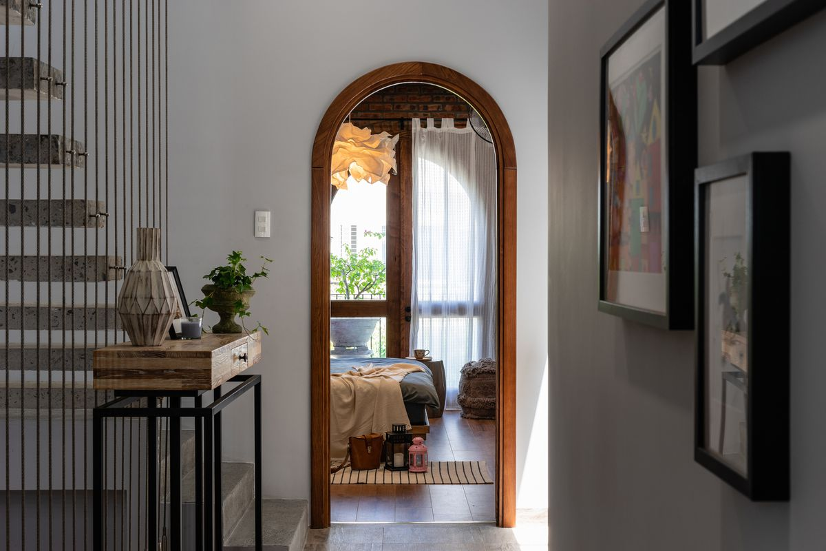 A wooden arched doorway leading to a bedroom. A floating stairway is on the left and hanging pictures are on the right.
