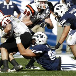 Brigham Young Cougars defensive end Graham Rowley takes down Idaho State Bengals quarterback Kevin Yost as Brigham Young University faces Idaho State in NCAA football in Provo, Saturday, Oct. 22, 2011.