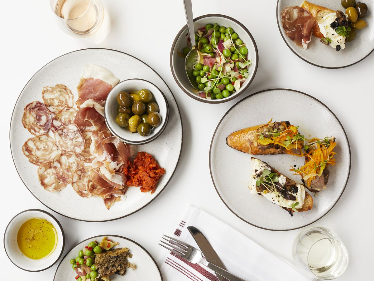 A spread of Italian dishes — including salumi, olives, and more — on a bright white surface