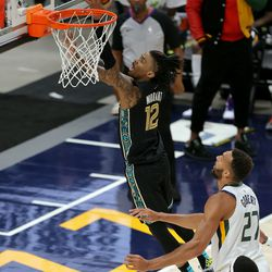 Memphis Grizzlies guard Ja Morant (12) gets up a shot ahead of Utah Jazz center Rudy Gobert (27) as the Utah Jazz and the Memphis Grizzlies play in game one of their NBA playoff series at Vivint Arena in Salt Lake City on Sunday, May 23, 2021.