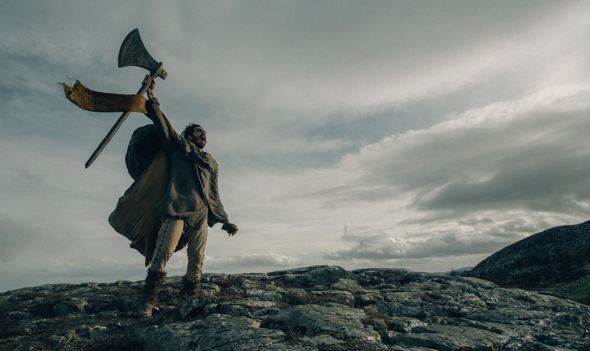 Dev Patel as Sir Gawain lifting an axe and shouting atop a mountain in The Green Knight