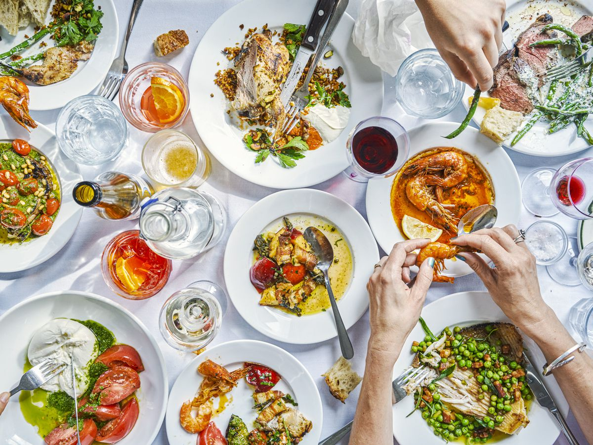 A spread of roast beef, roast chicken, tomatoes, burrata, and more with spritz and wine on a white tablecloth, shot from above