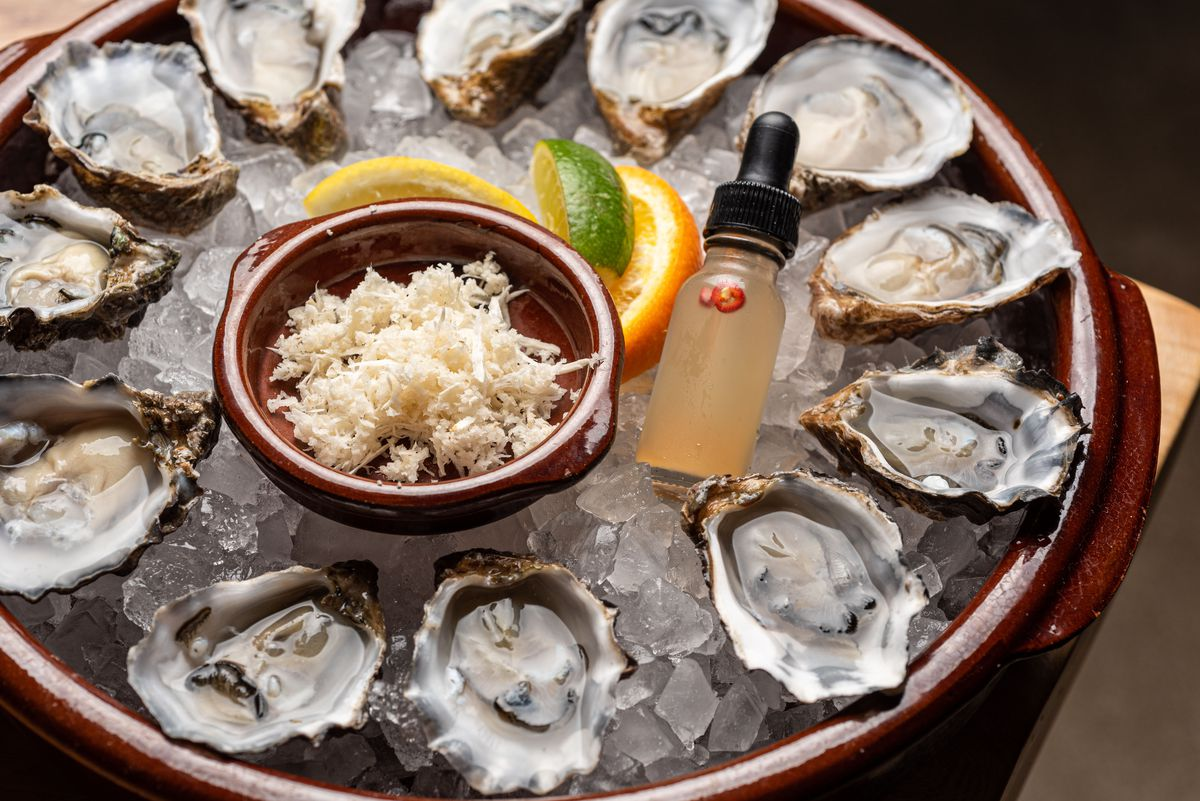 A tray of oysters in a dark brown tray on ice.