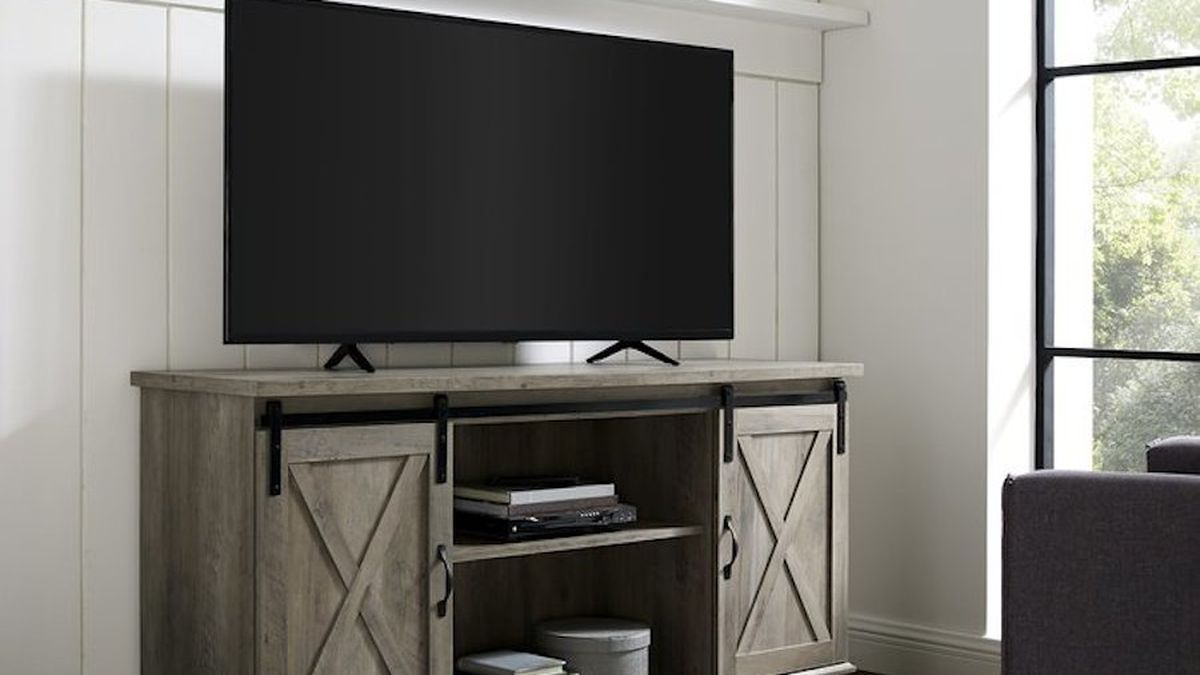 Rustic media console with sliding barn doors and a TV on top.