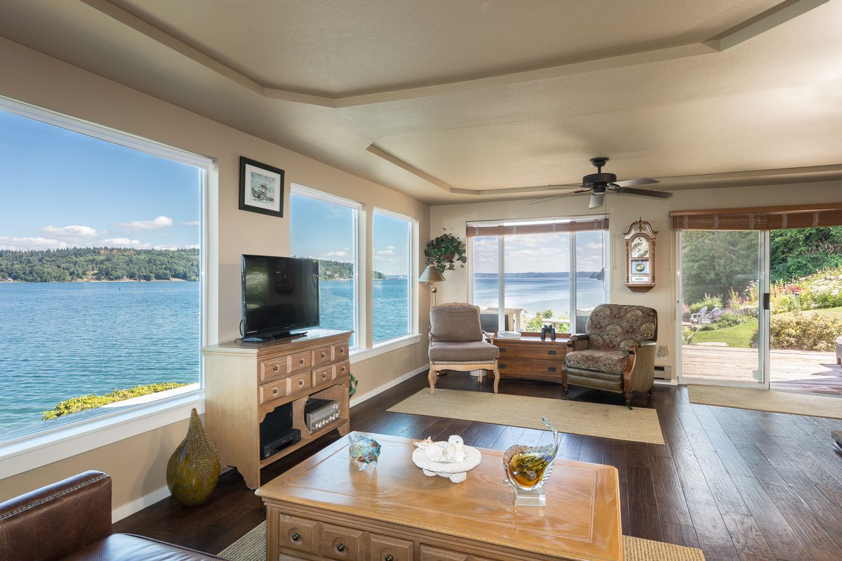 A living room with wide windows on two walls—left and far—overlooking the ocean.