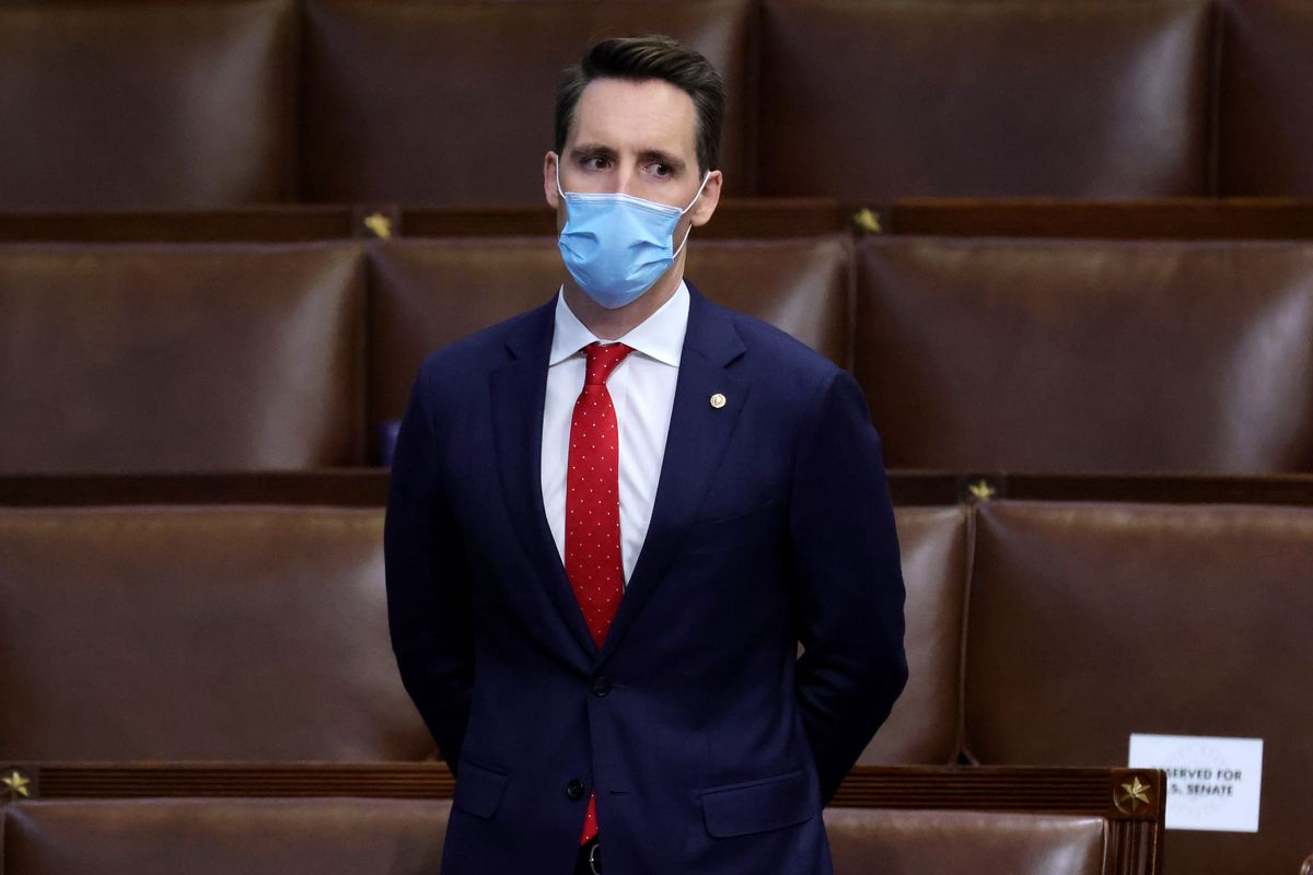 Hawley stands alone, masked, with his hands clasped behind his back.