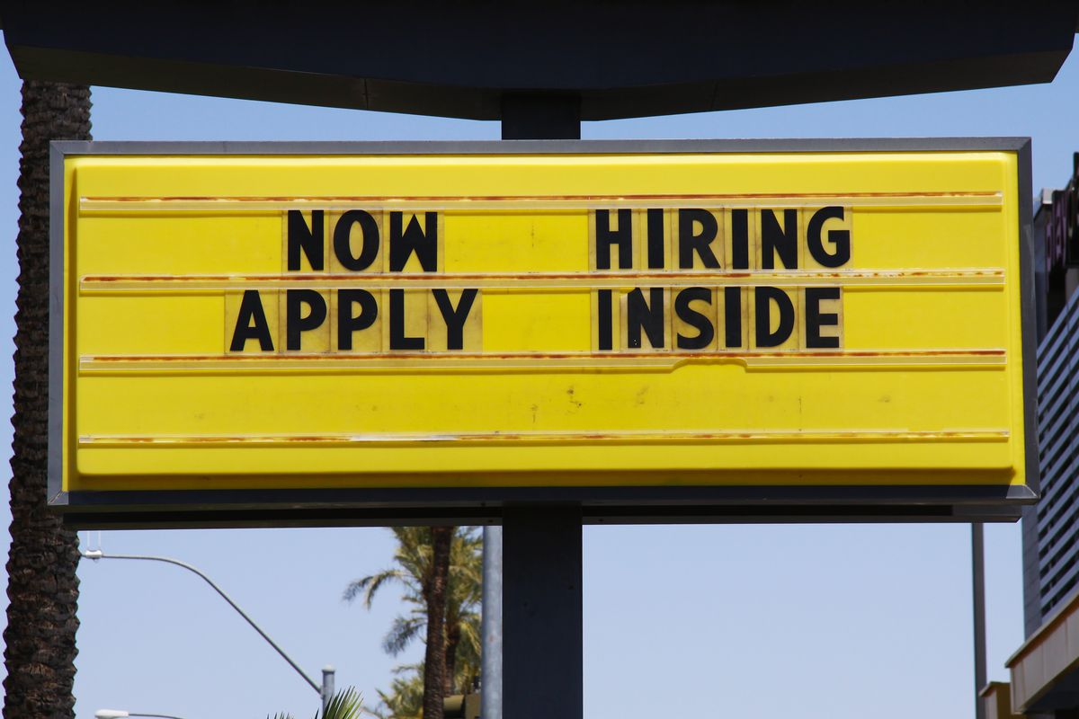 A yellow billboard saying Now Hiring Apply Inside against a blue sky and palm trees