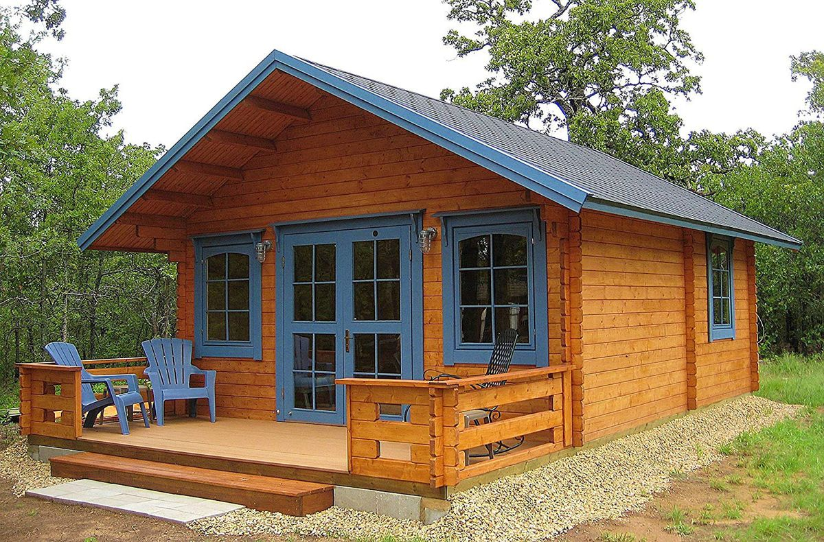 wooden cabin with front porch and blue trimmed windows.
