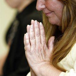 Debi Schmelzenbach participates in a blessing of hands ceremony.