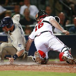 San Diego Padres' Nick Hundley, left, scores on a Luis Rodriguez base hit as Atlanta Braves catcher Brian McCann, right, cannot hang on to the ball.