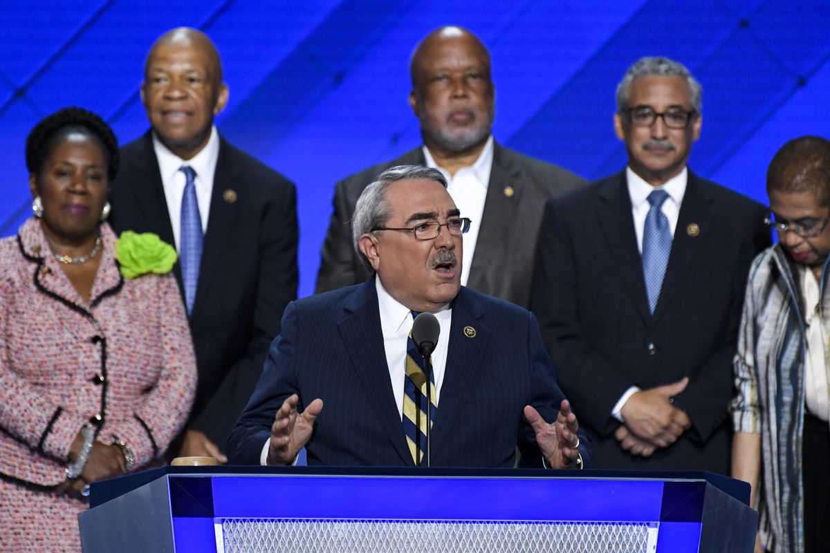 Members of the Congressional Black Caucus surround Congressman G.K. Butterfield, who is speaking from a podium