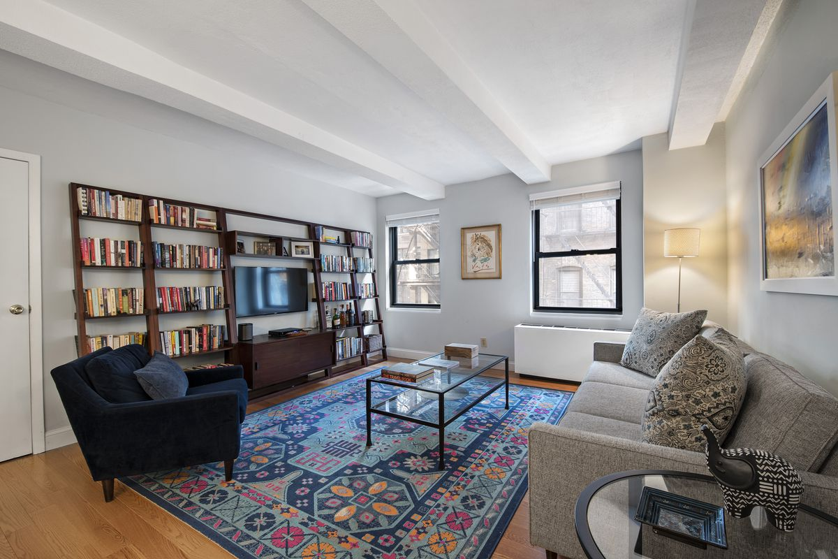 A living area with hardwood floors, beamed ceilings, several bookshelves, and a colorful rug.