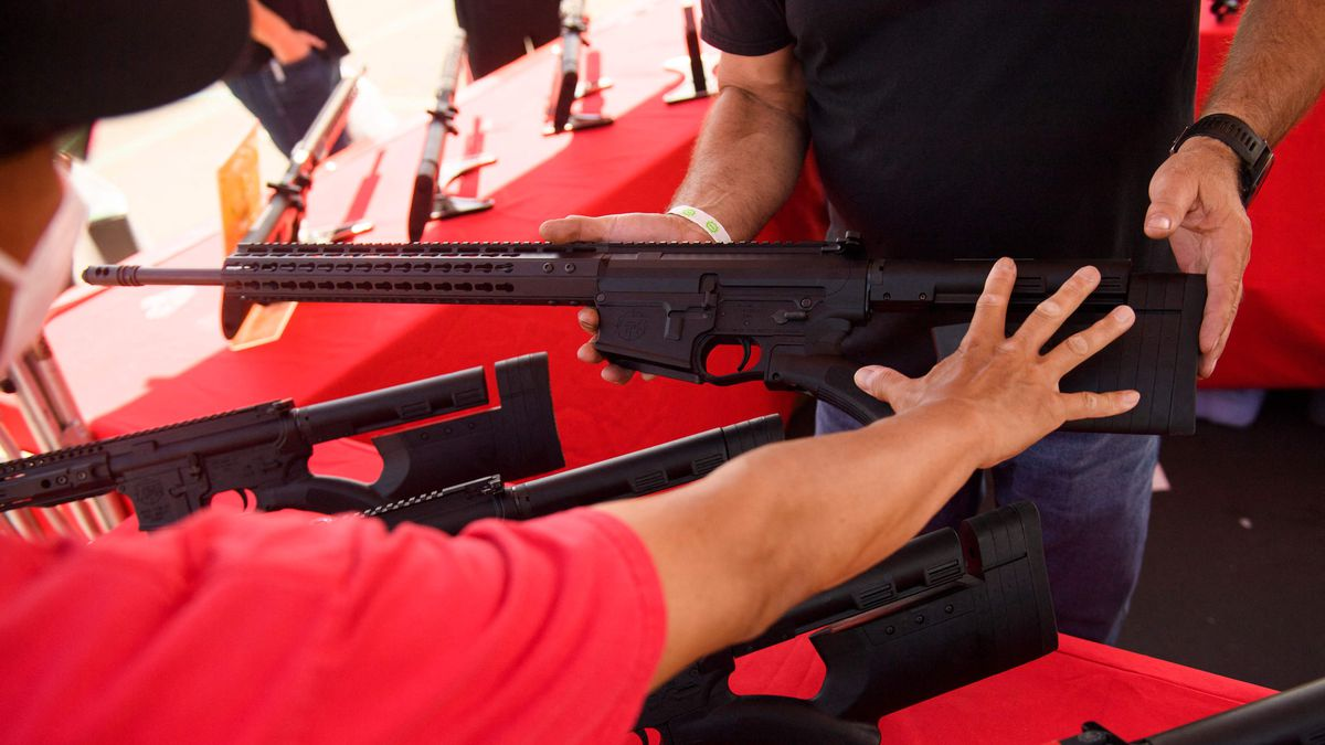 Gun sales leapt during the COVID lockdown, and a California judge just overturned that state's ban on assault weapons. Here, a clerk shows a customer a TPM Arms LLC California-legal featureless AR-10 style .308 rifle an Orange County gun show.