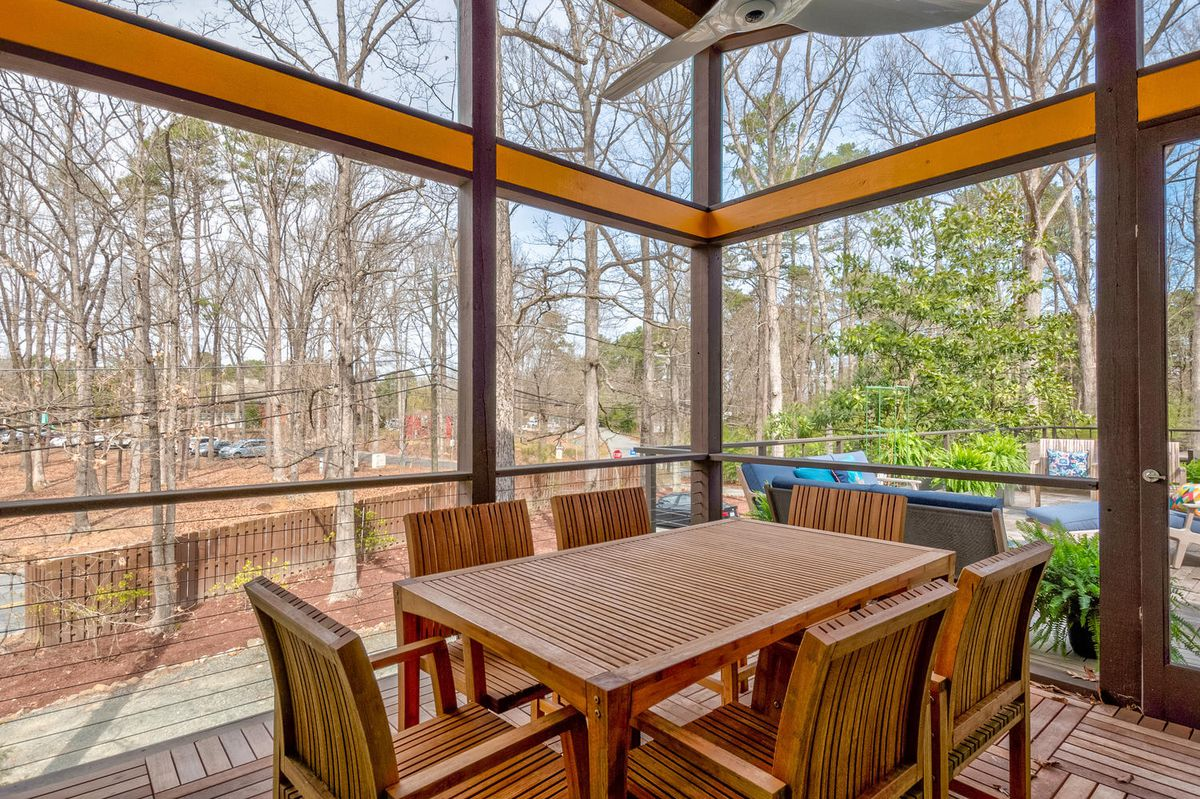A teak dining table and chairs sits in a screened-in porch.