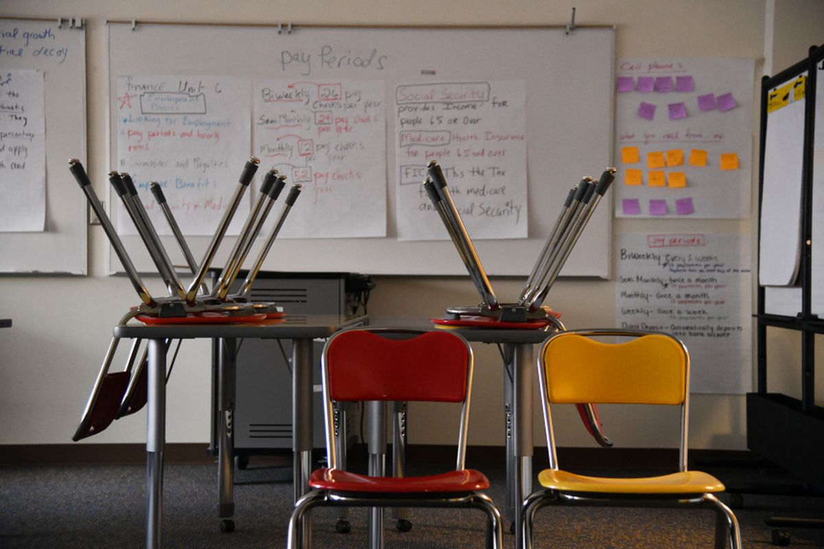 Chairs upside down on a table and two empty chairs sit in an empty classroom.