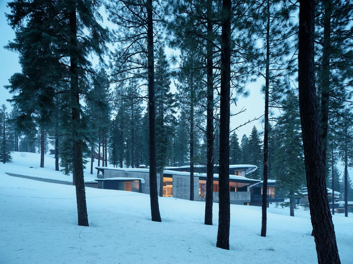 House on a snowy slope surrounded by trees.