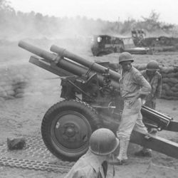 """One of twelve 105-mm howitzers of Wilber's battalion (152nd Field Artillery) fires """"over the American perimeter"""" in Aitape, New Guinea, August 4, 1944."""