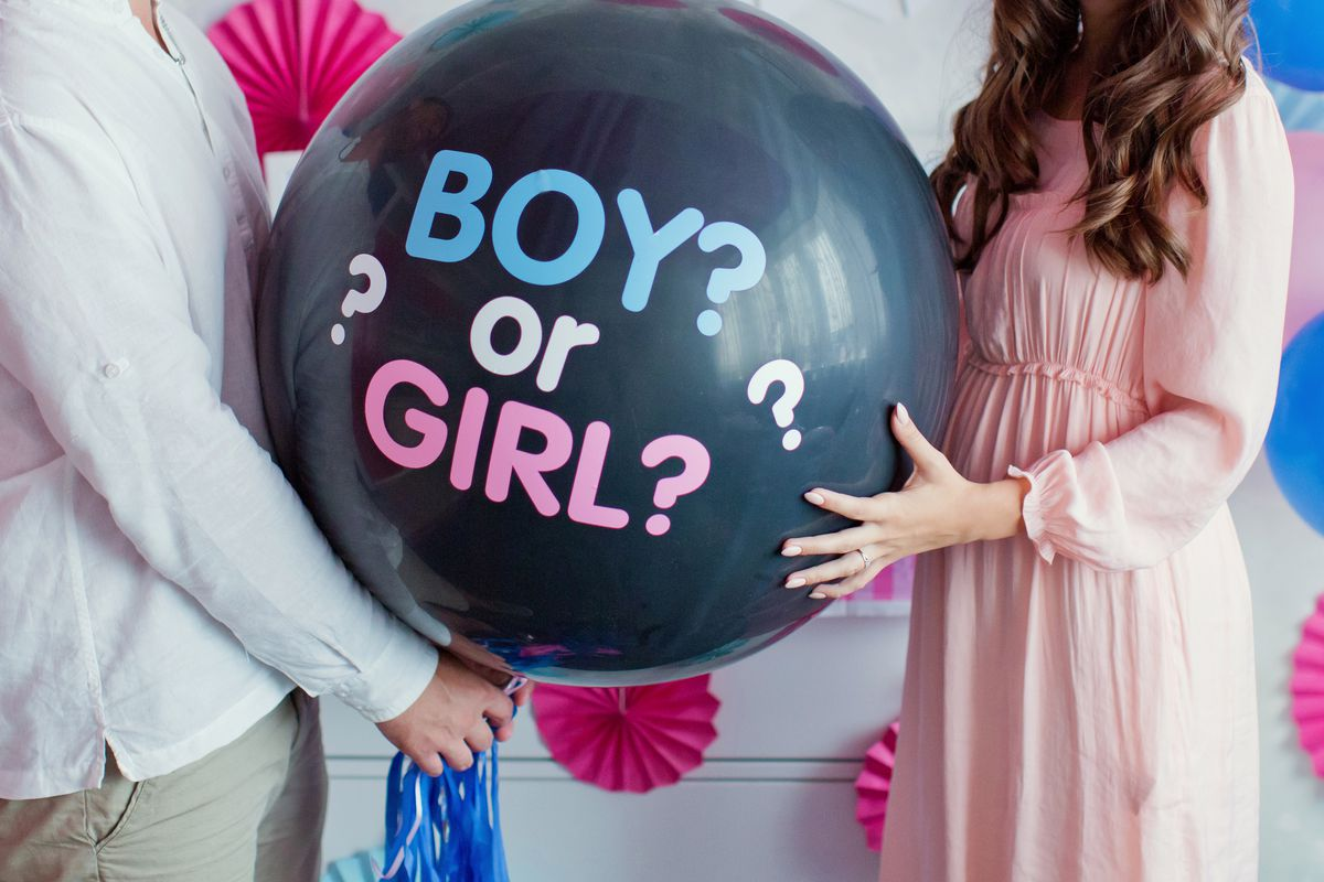 """Two people hold a balloon that reads, """"Boy or girl?"""""""