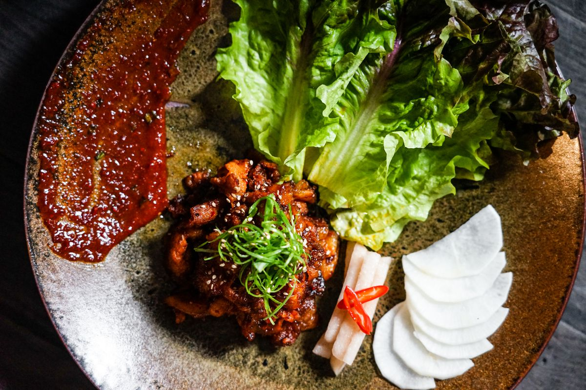 plate of korean ssam with pork, lettuce leaves, and red sauce on a brown plate