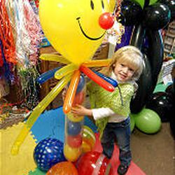 5-year-old Abby Bradley hugs a balloon clown display made up of 25 balloons. FunDaze \& HoliDaze also makes custom-ordered balloon people, monsters, snowmen and more.