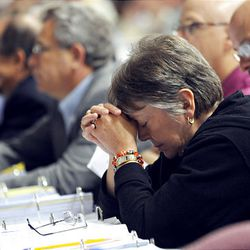 Voting member Janet Metcalfe, of Inver Grove Heights, MInn., pauses for a moment of prayer along with more than 1,000 members of the Evangelical Lutheran Chruch of America (ELCA) on Wednesday after a tornado warning was announced at the Minneapolis Convention Center.