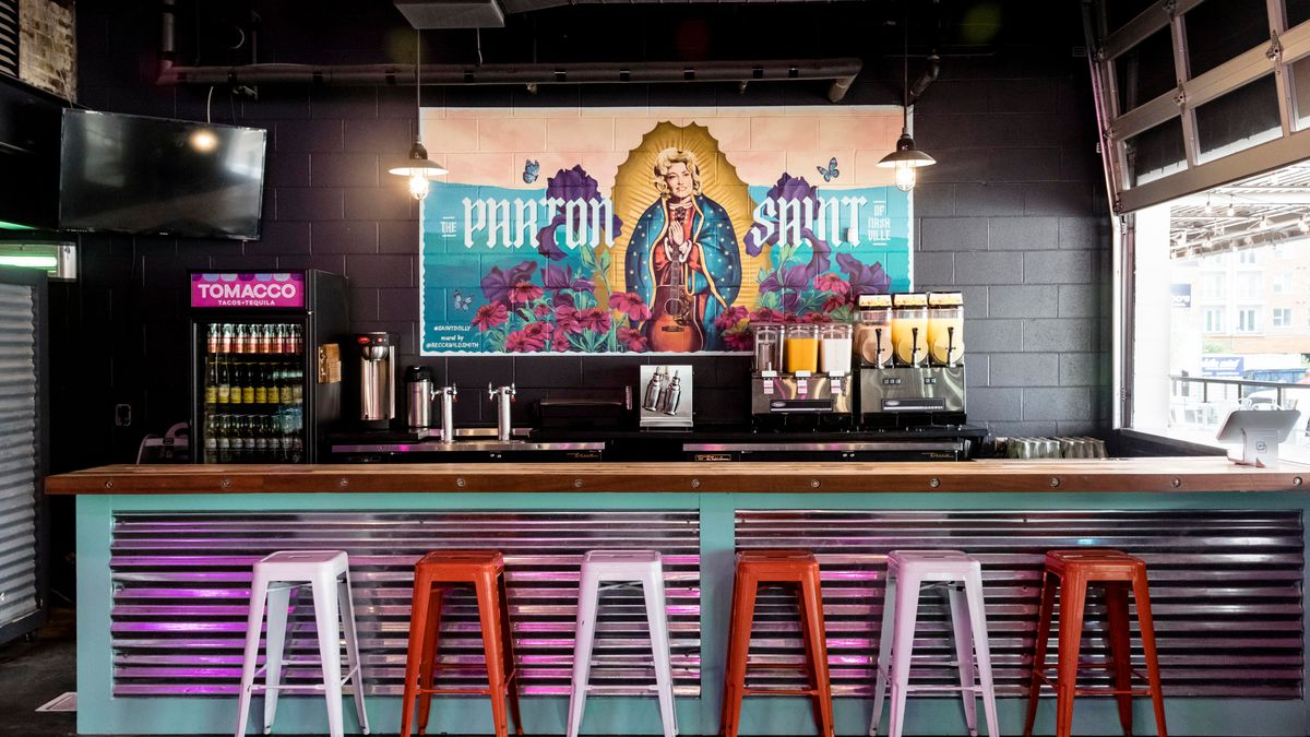 multi-colored bar stools in front of a purple metal covered bar, in front of dolly parton mural and drinks