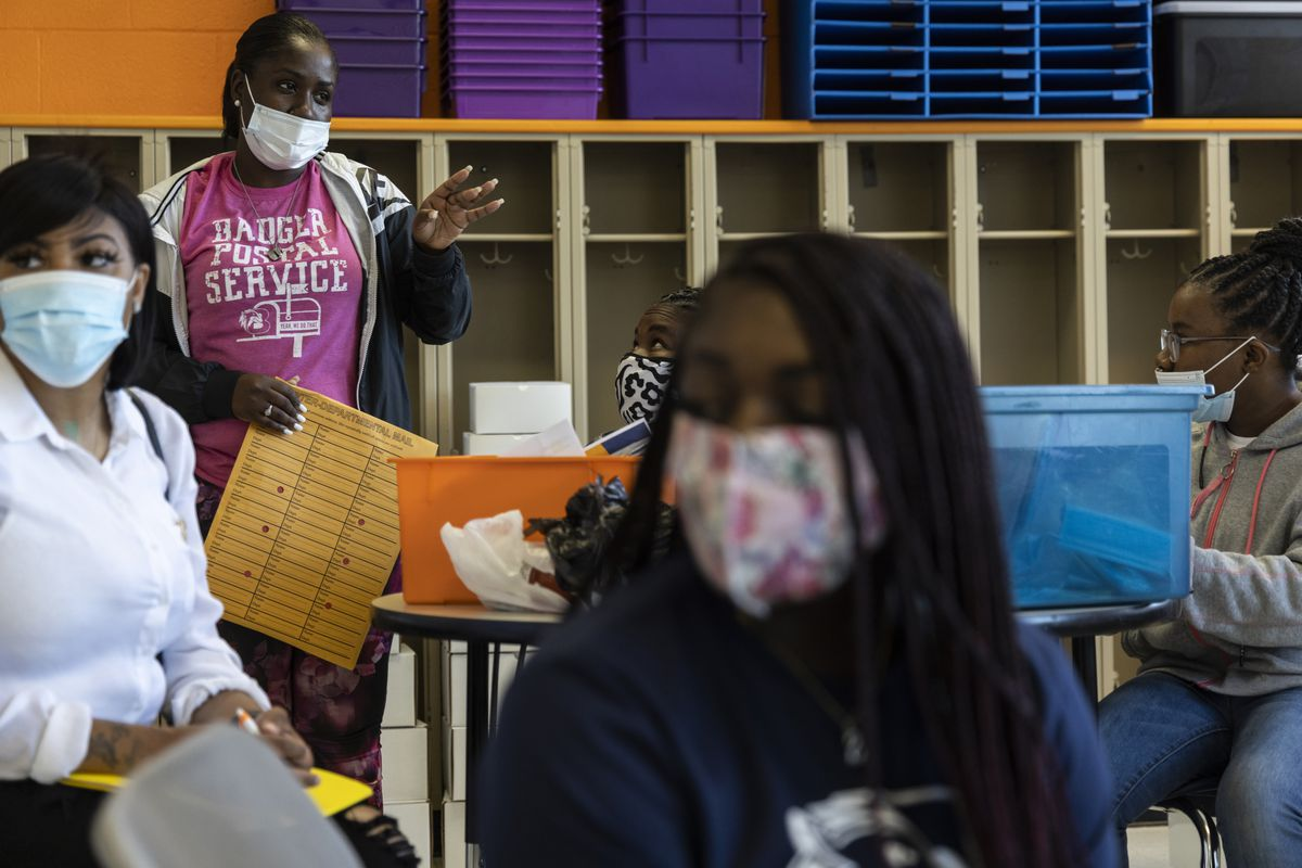 MEMPHIS, TN - April 15, 2021: Dominique Greer, second from left, speaks during a meeting for members of the Badger Postal Service program at Believe Memphis Academy. The Badger Postal Service program delivers meals and school supplies to the students of Believe Memphis Academy.