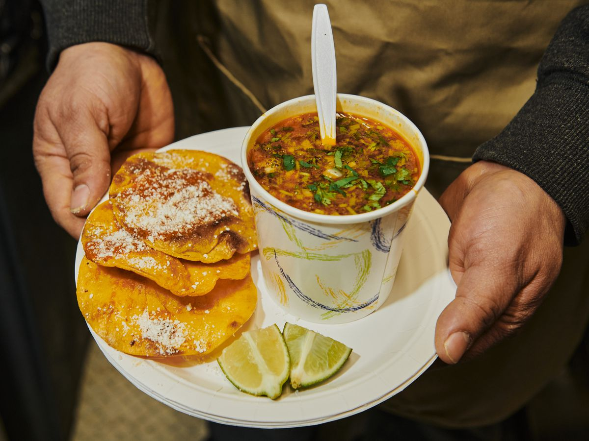 Two hands hold a disposable plate with three tostadas, a cup of brothy consomé, and two lime wedges.