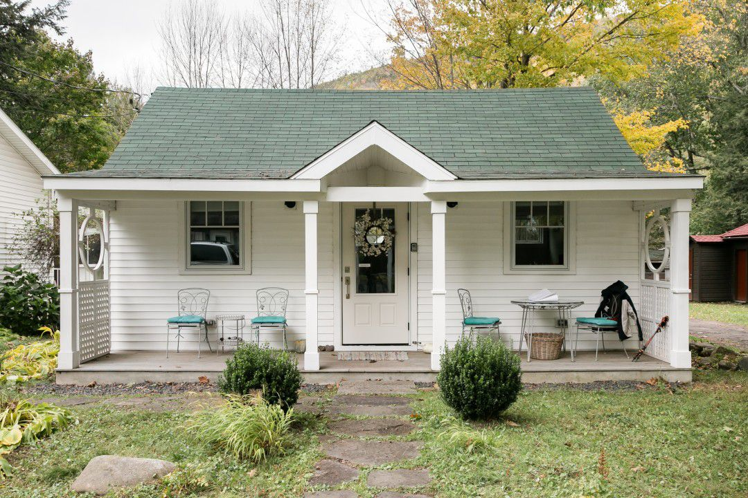 A small home with white siding, a front porch with tables and chairs, and a gray roof.